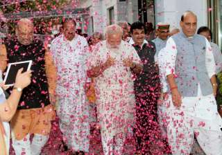 BJP workers shower flower petals on Prime Minister Narendra Modi, BJP president Amit Shah and senior leaders Rajnath Singh and M Venkaiah Naidu as they arrive at the party office in New Delhi on Thursday for a meeting after Assembly poll results.