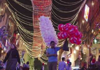 An Egyptian vendor looks for customers on a street decorated to mark the first day of the holy month of Ramadan in Cairo, Egypt. Devout Muslims throughout the world will begin to celebrate Ramadan.