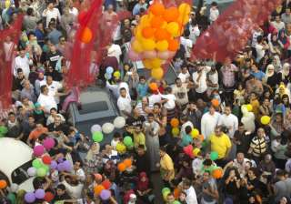 Egyptians wait to catch balloons distributed after Eid al-Fitr prayers, marking the end of the Muslim holy fasting month of Ramadan outside al-Seddik mosque in Cairo, Egypt.