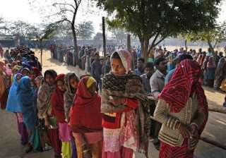 People wait in a queue to cast their votes at a polling booth in New Delhi, India.