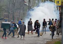 Youth pelting stones on security forces during