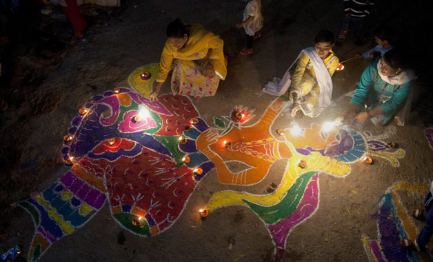 A family from the Hindu community light fireworks as they sit next to a traditional artwork outside their house while celebrating the Diwali festival, in Karachi, Pakistan.