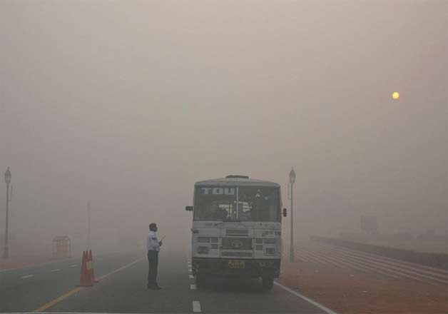 Traffic moves on a road covered by smoke and smog, on the morning following Diwali in New Delhi.