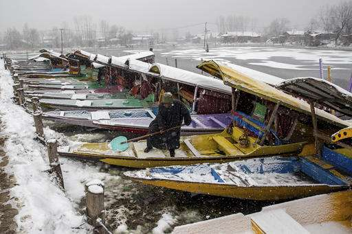 A Kashmiri man clears snow from his parked Shikara or traditional boat as it snows in Srinagar.