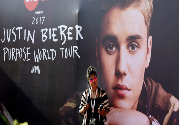 A fan stands in front of a picture of Justin Bieber ahead of his concert at the D Y Patil Stadium, Nerul in Mumbai. Biebers India fans were just crazy to get a glimpse of the singing sensation.
