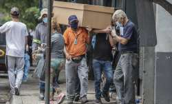 Cemetery workers carry the remains of a person in a cardboard coffin for burial at the General Cemet