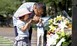 A man and his daughter pray for the victims of U.S. atomic bombing at the Atomic Bomb Hypocenter Pa
