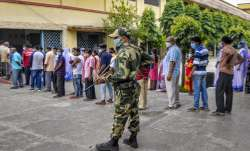 People stand in a queue to cast their votes at a polling